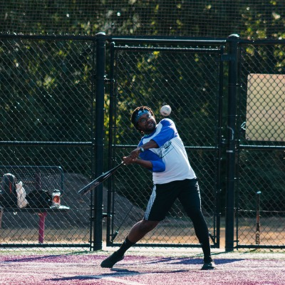 A softball participant swings at the ball as it approaches the bat.