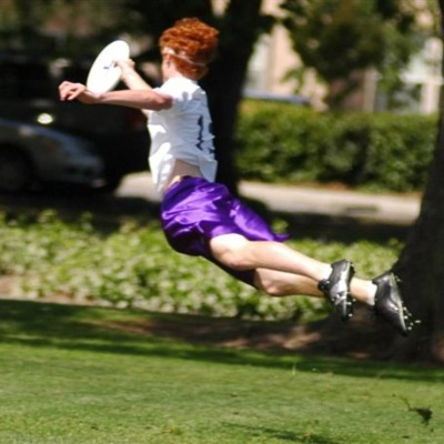 An ultimate disc play leaps through the air to catch a disc. The player wears purple shorts and has bright red hair.