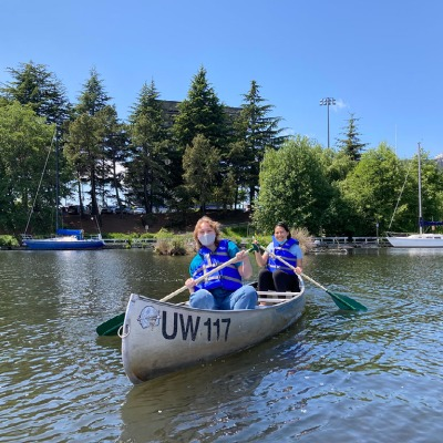 Two boaters paddle in a canoe. One is smiling, the other is masked. Behind them, trees and blue sky.