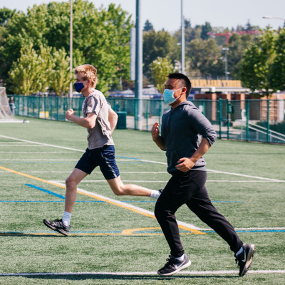 Two men wear masks while running across a Rec field at an Outdoor Boot Camp fitness class.