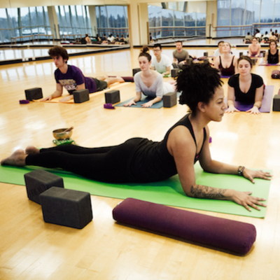 A yoga instructor models a pose in front of a group of participants in the IMA studio.