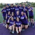 Softball team Champs Backdoor Sliders gather smiling on the field wearing purple Champs shirts.