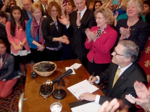 Onlookers cheer as Governor Inslee signs SB 6523.