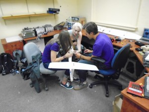 """(From left to right) Hannah Olliges, Madison Mackenzie and Max McDonald inserting instruments into the """"Little Wing"""" UAS"""