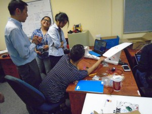 """(From left to right) Dr, Lum, Gizelle Gando, Jessica Trinh, and Jennifer Look working on the instruments inside the """"Exodia"""" UAS"""