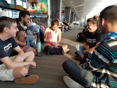 David Rufin, Kidus Yohanes, Tiffany Hu, Yuliana Flores, Richard Parra [left to right] sit down to play cards while we wait for our time to board the plane.