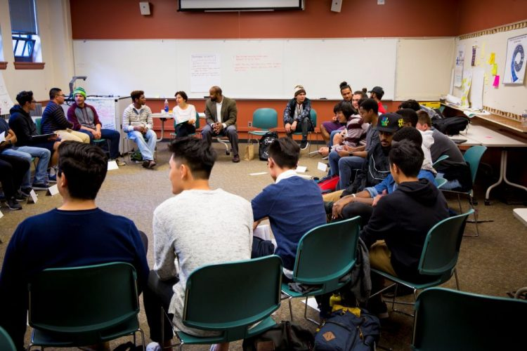 Group of young men of color sitting in a circle.