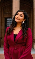 Ruby Ayub in a red outfit posing in front of a building