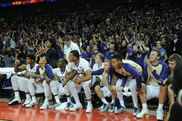 The men's basketball team leaps from the bench at the final whistle