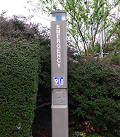 tall, brown emergency phone tower located near walkway