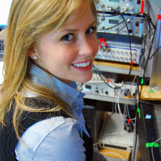 Female undergrad student smiling and sitting in front of electronic circuits
