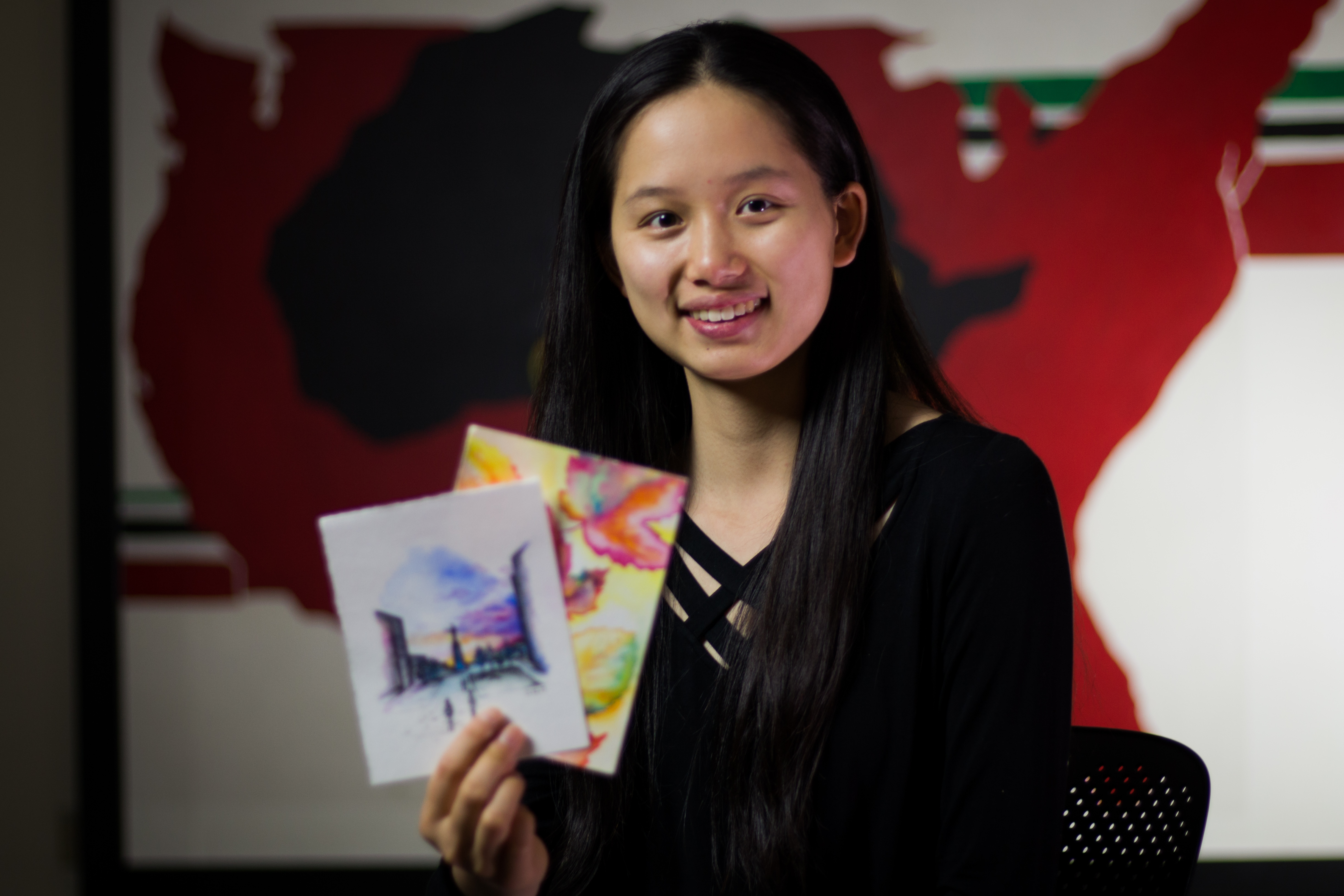 Grace Wang holds her drawings.