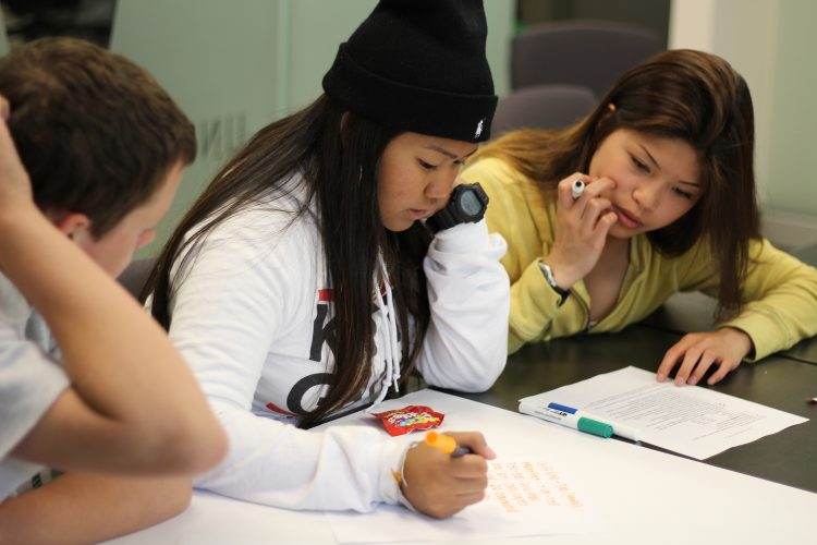 Photo of two students working together on a paper