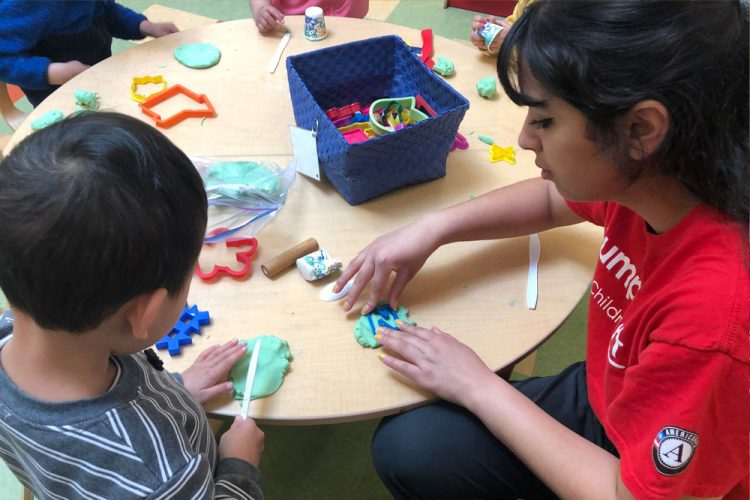 Photo of undergraduate working with preschooler