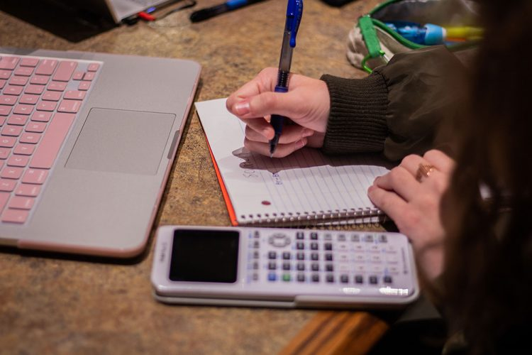 Photo of student writing in notebook, calculator and laptop