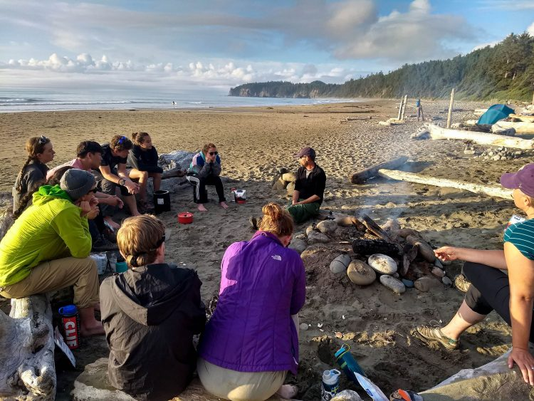 Photo of students on the beach listening to Dave Conca