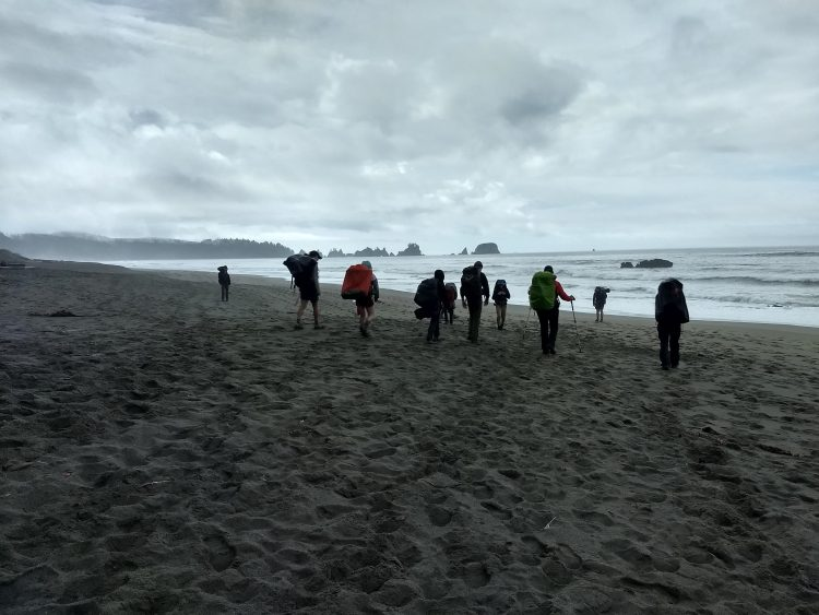 Students backpacking on the beach