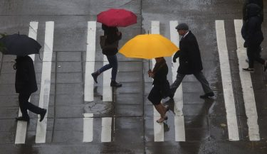 people crossing a city street in the rain with umbrellas