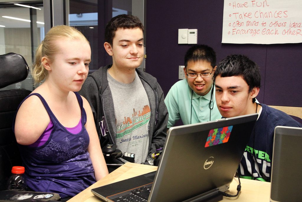 Four students gathered around a computer
