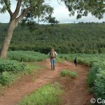 Young woman and black lab walking along a dirt road in a remote area