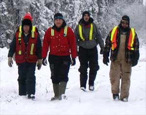 four researchers in heavy winter clothing walk through the snow in the woods