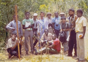 a group of men stand in a clearing among trees with various tools