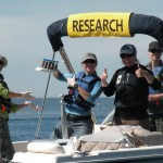Four researchers on a boat holding up a whale poop in container