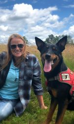 Woman sits in a field of grass with black and tan dog