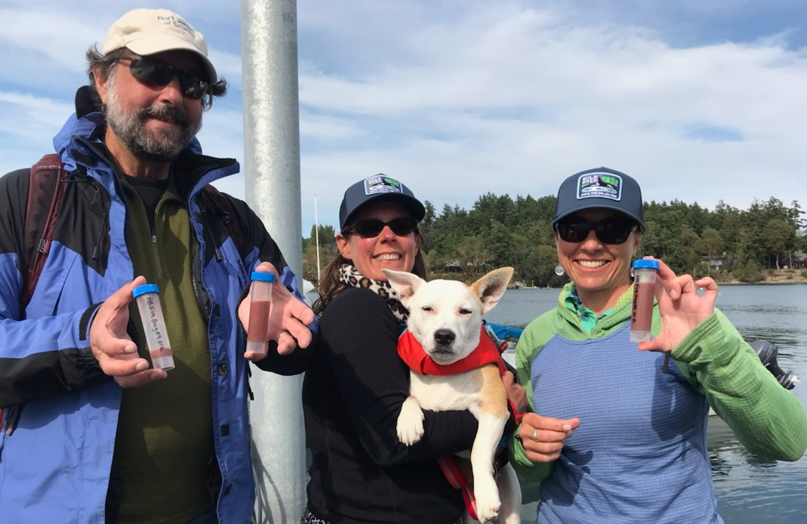 Two women and a man stand with a dog held up along with vials of whale scat.