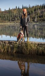 Woman stands on jetty in lake with a brindle colored dog