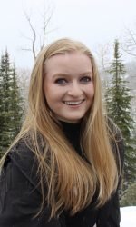 Smiling young woman with long blonde hair wears black jacket and stands on a snowy landscape