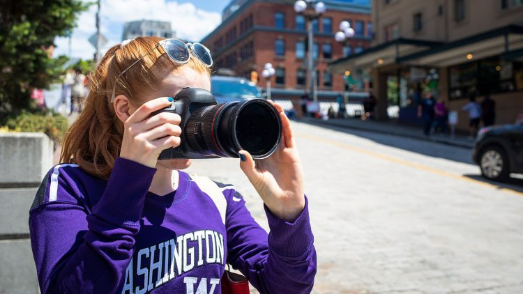 A woman in a UW shirt takes a picture on a downtown street corner.