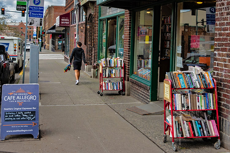 Outside shot of bookstore on the Ave with sandwich board and person walking on the sidewalk.