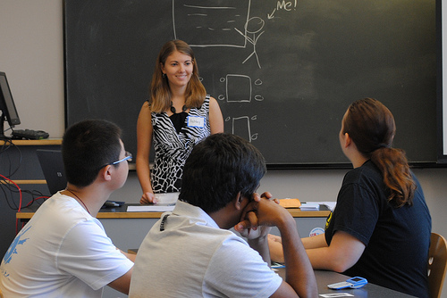 Professor standing in front of chalkboard, smiling and listening to a student ask a question from the audience.