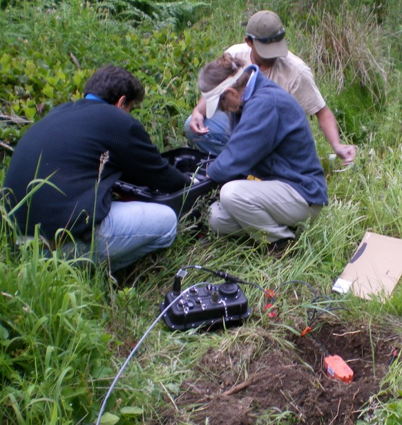 "A seismic sensor (orange device) and datalogger (black box) are installed as part of one station in the ""array of arrays"" on the Olympic Peninsula in Washington state. The researchers are, from left, Danilo Galluzzo of Italy's Istituto Nazionale di Geofisica e Vulcanologia, Noel Barstow of the Iris/Passcal Instrument Center and Abhijit Ghosh of the UW. (Credit: Lisa Foley, Iris/Pascal Instrument Center)"