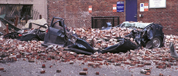 A small car and a van lie crushed under bricks that fell from a Seattle building during the Nisqually Earthquake on Feb. 28, 2001. (Photo credit: Federal Emergency Management Agency)