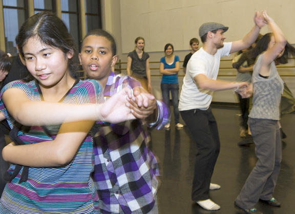 Amazing Grace students Fherna Caoili and Isaac Abraham dance in the foreground, while UW students Casey Duranleau and Erika Najarro practice their moves behind them. | Photo by Kathy Sauber