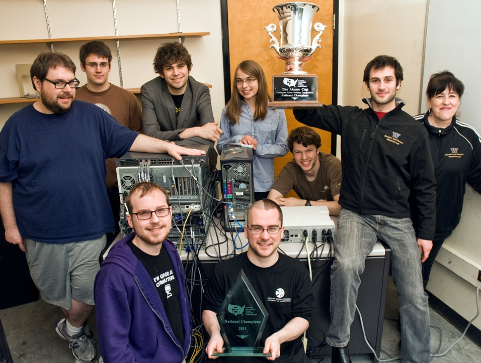 The winning team for the National Collegiate Cyber Defense Competition, posing in their makeshift training room in Sieg Hall. Back row: Karl Koscher (co-captain), Conrad Meyer, Ian Finder, Mary Pimenova, Cullen Walsh, Alexei Czeskis (holding trophy, captain), Melody Kadenko (team adviser). Front row: Mark Jordan, Baron Oldenburg.