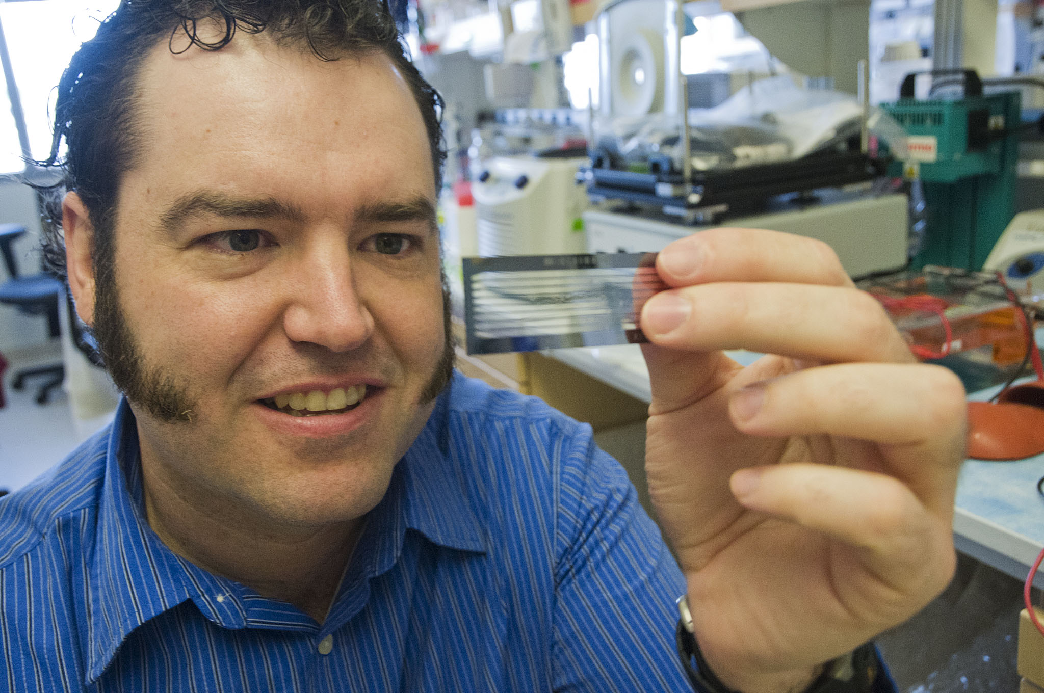 Dr. Brian O'Roak holds a flow cell on which DNA samples are loaded for sequencing. The imaging and chemical analysis of the sample all take place on the slide.