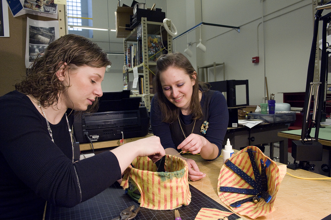 Graduate design students Emily Van Winkle, left, and Rachel Apatoff work on a model for a Canterbury Tales design.