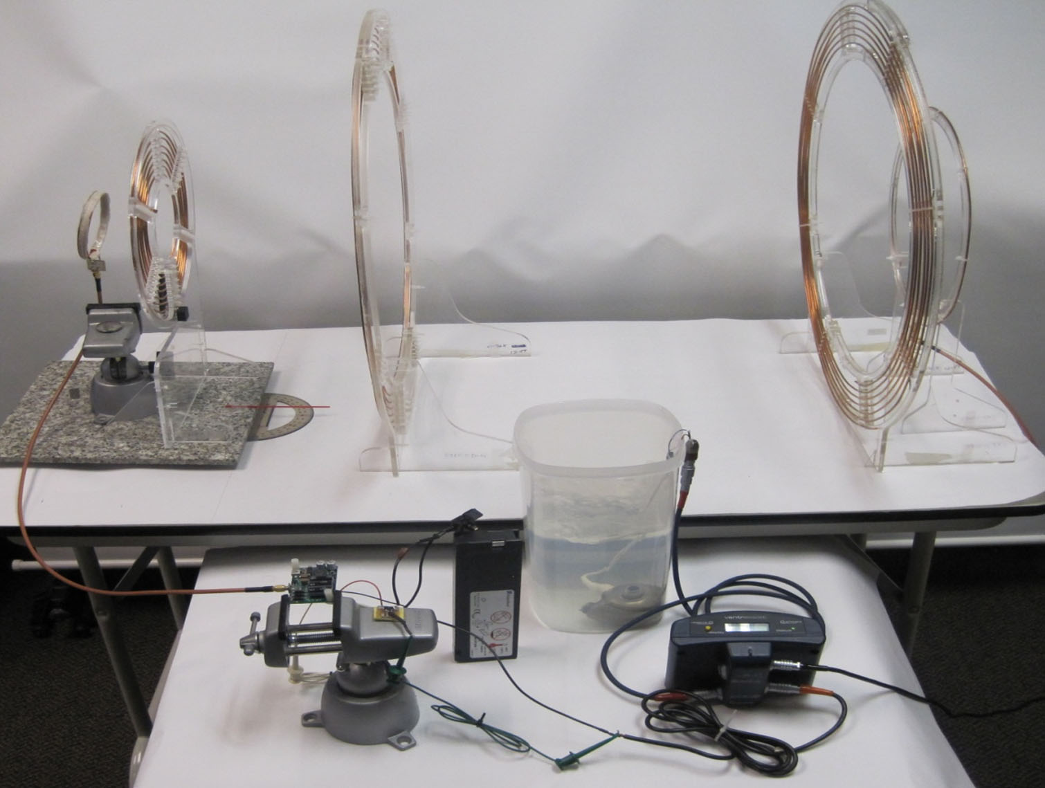 The experimental setup has a large transmission coil, at the right, connected to the building's electricity. At the left is the receiving coil, and near it is a smaller coil connected to a commercial heart pump sitting in a jar of fluid.
