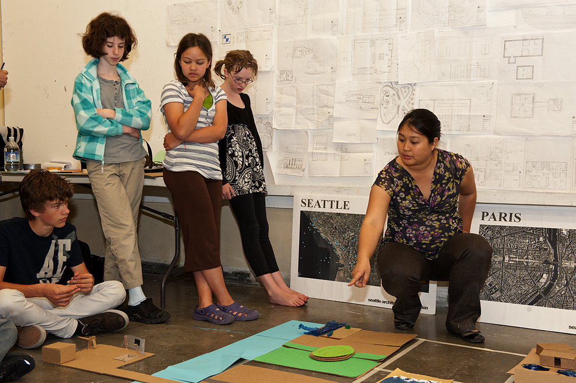 Instructor Joanne Lee discusses the developments in her UW Summer Youth Programs class in community architecture. With her are (from left)student participants Sam Tudor-Hidy, 13; Joanne Lee, instructor for UW Summer Youth Programs' class in community architecture, looks over the group's growing development. Watching with her are (from left)student participants Sam Tudor-Hidy, 13; Megan Rochlin, 12; Sage Minard, 12; and Adrianne Jacobsen, 11.