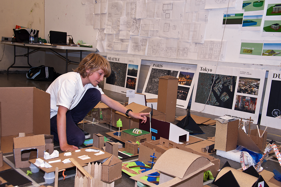 Henry Watts, 13, adjusts his addition to a cardboard city built as part of the Summer Youth Programs class called Community Architecture: Solving Social and Environmental Issues Through Design. His working partner was Jordan Broihie, also 13.