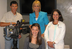Greer Gates (center, seated) is all smiles, flanked by KOMO News' Neil Ikeda and Michelle Esteban, and UW Medicine's Liz Swisher.