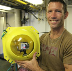 """Matthew Alford holds the """"crush cam,"""" a Go Pro camera housed inside a glass sphere able to withstand pressures deep in the ocean."""