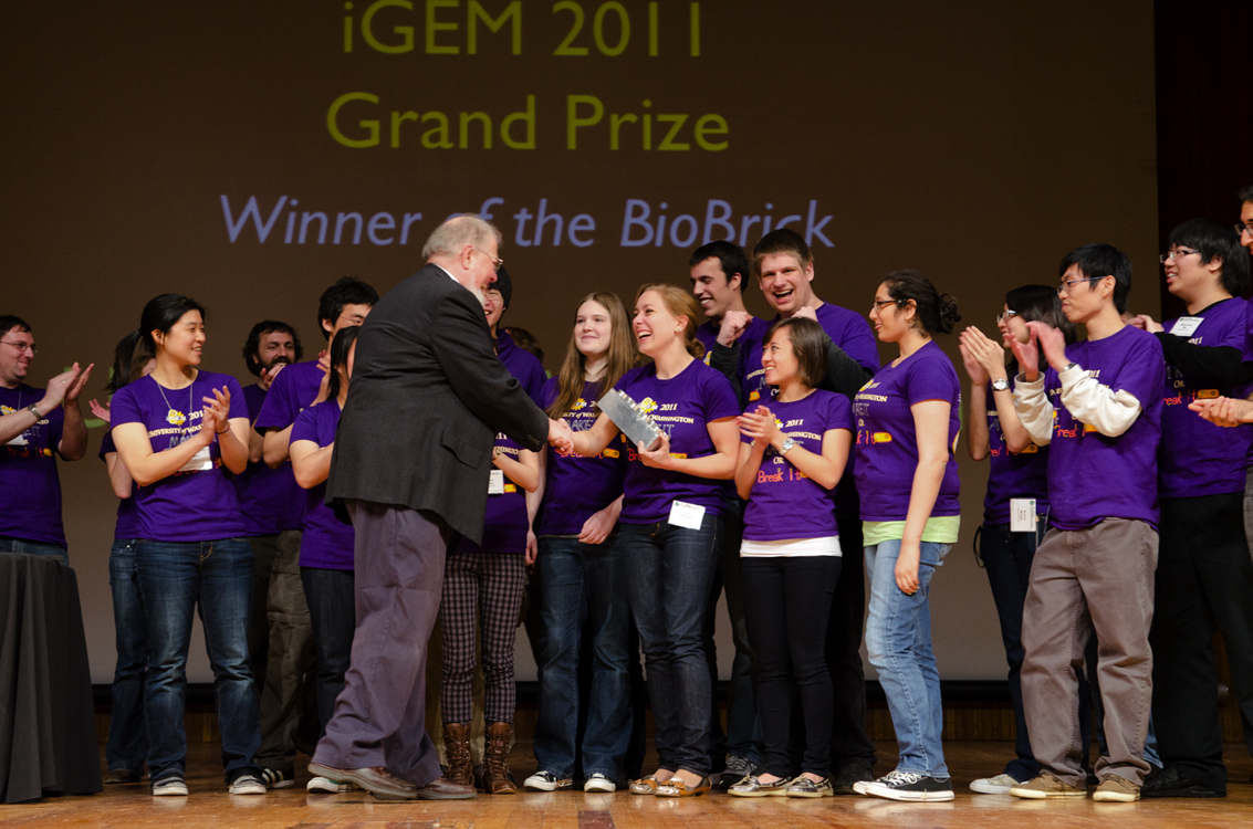 Liz Stanley, a senior majoring in microbiology, accepts the brick trophy on a Boston stage Nov. 7 for the iGEM team's 'World Champion' win in genetic engineering. The brick is a symbol of the molecular components that are used in synthetic biology.