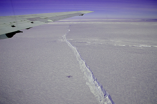 A photo from the window of a NASA aircraft shows the rift across the Pine Island Glacier ice shelf running off toward the horizon. The plane flew across the crevasse on Oct. 26, 2011 as part of Operation IceBridge, taking detailed measurements of depth, width and shape. The ice shelf has not calved a major iceberg since 2001.