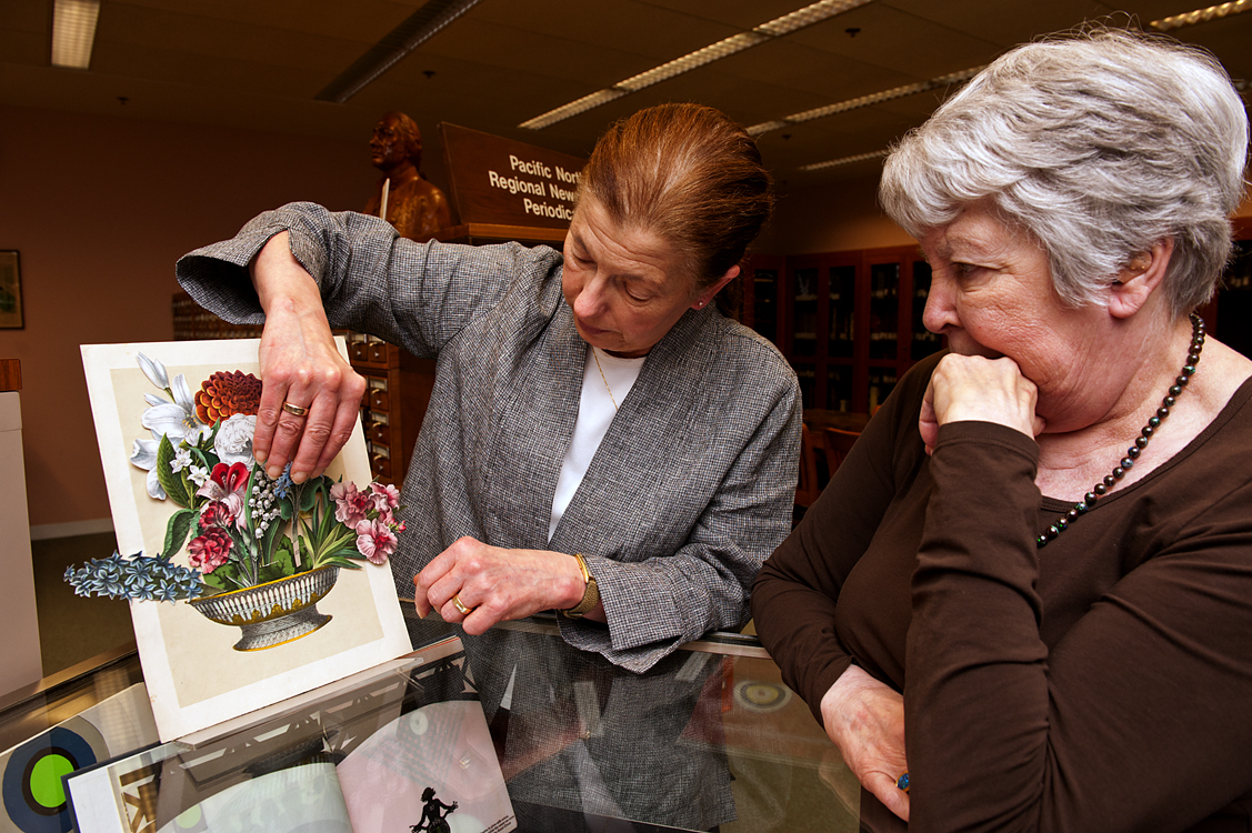 Sandra Kroupa, left, and donor Pamela Harer, with a 19th century children's flower-arranging guide titled 'The Realm of the Queen of Flowers,' where about 50 different flowers can be inserted in slots.