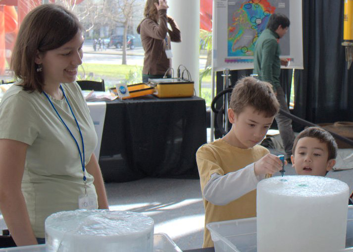 Taryn Black, a UW undergraduate, coaches two young visitors conducting an experiment to find out which block of ice is from fresh water and which from salt water.