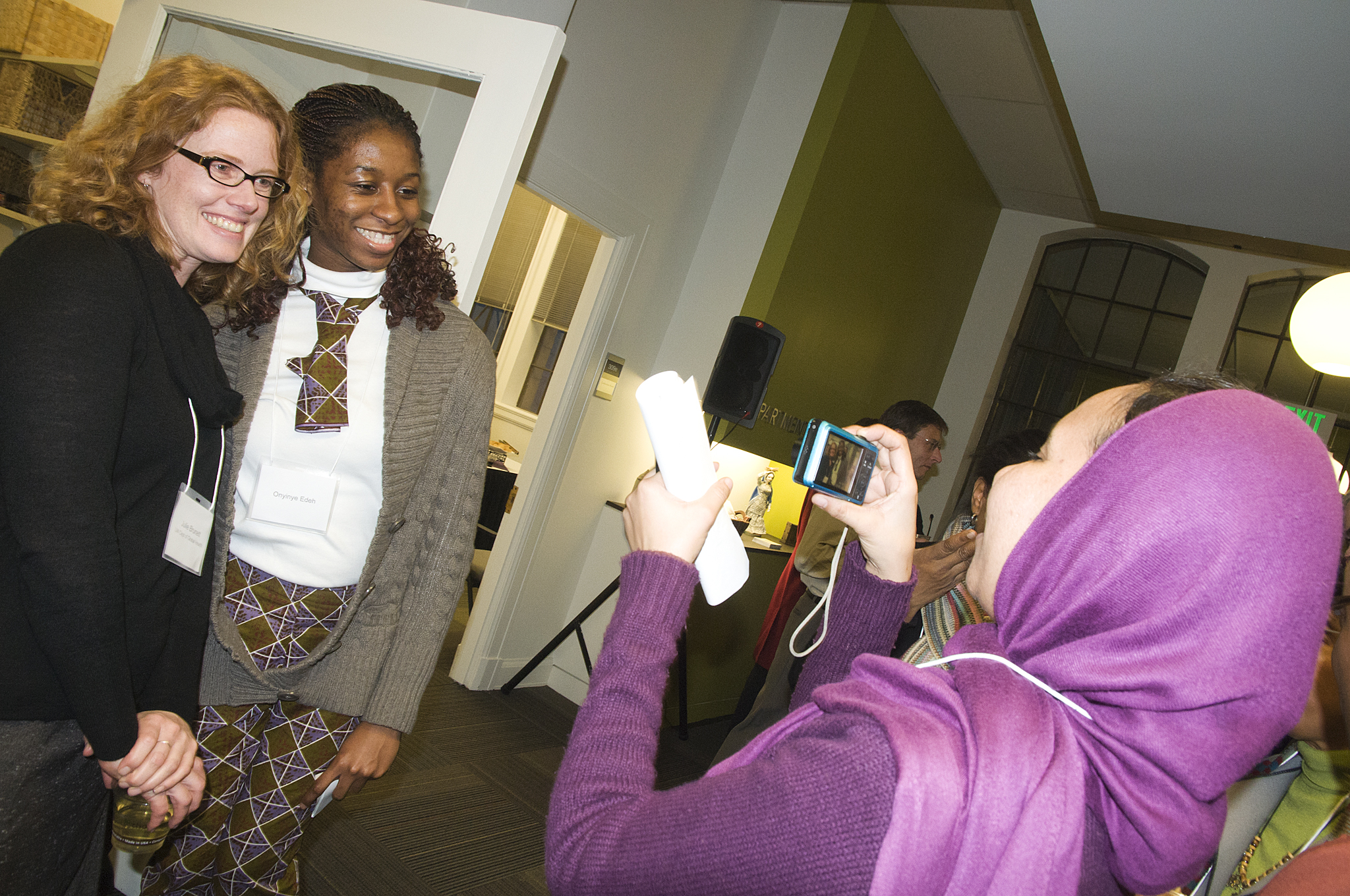 Amel Omer, a public health student from Sudan, photographs graduate student adviser Julie Burnett and Oninye Edeh, a fellow student from Nigeria at the Department of Global Health Open House.